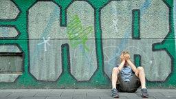 Ein Junge sitzt mit den Händen vor dem Gesicht an einer Häuserwand voller Graffiti. © Chromorange Foto: Walter G. Allgöwer