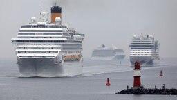 Auf der Ostsee vor Warnemünde nehmen drei Kreuzfahrtschiffe Kurs auf die Einfahrt zum Seekanal. © dpa-Bildfunk Foto: Bernd Wüstneck