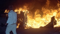 Ein Mann steht am 27.8.1992 vor brennenden Pkw auf einer Straße am Asylbewerberheim in Rostock-Lichtenhagen. © dpa Foto: Bernd Wüstneck