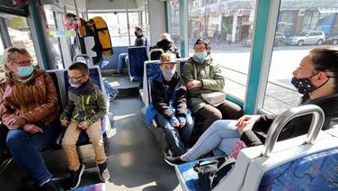 Rostock: Fahrgäste sitzen mit Mund-Nasenbedeckungen in einer Straßenbahn. | dpa-Bildfunk