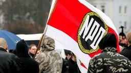 Demonstranten schwenken eine NPD-Fahne. © picture-alliance/CHROMORANGE Foto: Christian Schwier