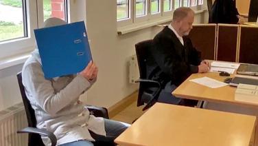 In einem Gerichtssaal des Landgericht Stralsund sitzt ein Angeklagter hinter einem Tisch und hält sich einen blauen Aktenordner vor das Gesicht. | NDR