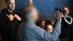 Der Angeklagte (M.) beim Prozess in Schwerin. © dpa Foto: Danny Gohlke