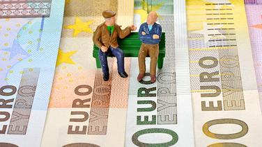 Zwei Rentner-Figuren sitzen auf einer Parkbank, die symbolisch auf Geldscheinen steht. © dpa-Zentralbild Foto: Eibner-Pressefoto