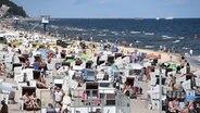 Touristen nutzen das hochsommerliche Wetter am Strand auf der Insel Usedom zum Sonnen und Baden. © dpa-Bildfunk Foto: Stefan Sauer