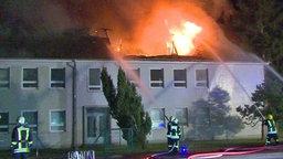 In Trassenheide auf Usedom versucht die Feuerwehr den Brand einer geplanten Flüchtlingsunterkunft zu löschen.  Foto: Tilo Wallrodt