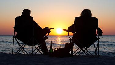 Urlauber genießen Sonnenuntergang am Meer | dpa-Bildfunk