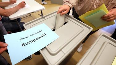 In einem Wahllokal gibt eine Wählerin ihre Stimme für die Europawahl ab. | dpa