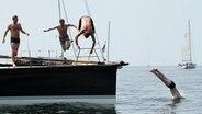 Männer springen vom Boot in die Ostsee. © warnemuender-woche.com Foto: Pepe Hartmann