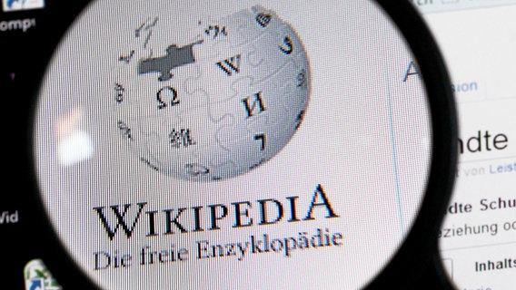 Unter einer Lupe ist der Schriftzug und das Logo des Online-Lexikons Wikipedia auf einem Computerbildschirm zu sehen. © dpa-Bildfunk Foto: Jens Büttner