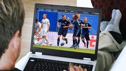 Ein Mann schaut am Laptop eine Fußballübertragung (Bildmonatge) © fotolia, picture alliance / dpa Foto: sculpies, Axel Heimken