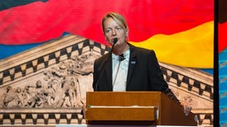 Dana Guth hält eine Rede vor einer Kulisse aus AfD-Schriftzügen, deutscher Flagge und Reichstagsgebäude © dpa Picture Alliance Fotograf: Philipp Schulze