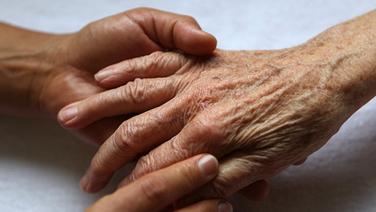 Eine Pflegerin massiert die Hände einer Seniorin. © dpa-Bildfunk Fotograf: Oliver Berg