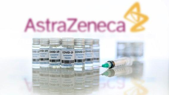 Caixas de vacinação e seringas estão em uma mesa em frente ao logotipo da AstraZeneca. © picture alliance / Geisler-Fotopress. Dwi Anoraganingrum