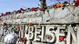 Blumen an einem Gedenkstein in Bergen-Belsen. Archivbild 2013. © picture-alliance/ dpa/dpaweb Foto: Rainer Jensen