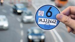 """Eine Hand hält einen Designvorschlag der """"Blauen Platette"""". © picture alliance / dpa Fotograf: Bernd Weissbrod"""