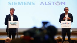 Der Geschäftsführer von Alstom, Henri Poupart-Lafarge (r.), und der Geschäftsführer von Siemens, Joe Kaeser, sprechen auf einer Pressekonferenz in Paris. © dpa-Bildfunk Fotograf: Thibault Camus