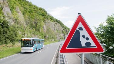 """Ein Bus fährt über die Bundesstraße B83 zwischen Bodenwerder und Holzminden vorbei an Felsen am Naturschutzgebiet """"Mühlenberg bei Pegestorf"""". © dpa-Bildfunk Fotograf: Julian Stratenschulte"""