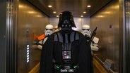 Darth Vader mit Sturmtruppe (Kostüme) in einem Fahrstuhl. © UMG