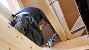 Ein Berufsschüler arbeitet am Dachstuhl eines Fachwerkhauses. © Photo Burkhardt Foto: Astrid Burkhardt