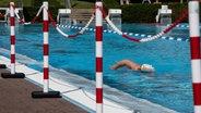 Eine Person schwimmt in einem Freibad. © dpa - bildfunk Foto: Swen Pförtner