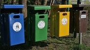 Mülleimer für Glas, Karton, Plastik und Restmüll hängen nebeneinander. © NDR Foto: Carmen Woisczyk