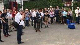 Eine Gruppe von Leuten steht auf einem Platz, einer schaut durch eine Fotokamera © NDR Fotograf: Wilhelm Purk