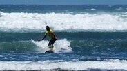 Sohal Behmanesh surft mit den Wellen. © NDR Foto: Marco Schulze