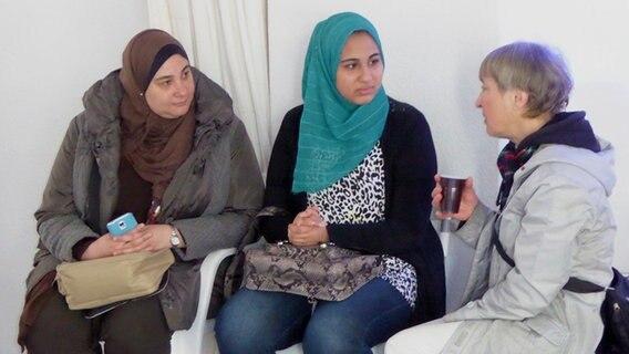 Zwei Frauen mit Kopftuch sprechen mit einer älteren Dame. © NDR Foto: Sebastian Deliga