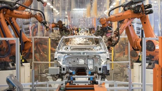 Teile eines VW-Passats werden in einer Produktionsstraße im Volkswagen Werk Emden von Robotern zusammengefügt. © dpa/picture-alliance Foto: Jörg Sarbach