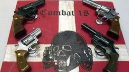 """Auf einem Tisch liegt eine Flagge mit der Aufschrift """"Combat 18"""" und Totenkopf, darauf liegen vier Pistolen. © dpa - Bildfunk Foto: Horst Pfeiffer"""