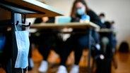 Eine Mund-Nasen-Maske hängt an einem Tisch im Klassenzimmer. © picture alliance/Eibner-Pressefoto/Weber/Eibner-Pressefoto Foto: Weber/Eibner-Pressefoto