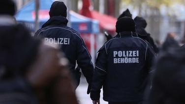 Zwei Polizisten laufen durch eine Innenstadt. | picture alliance