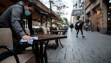 Ein Mitarbeiter wischt Tische vor einem Cafe in einer Innenstadt ab. | picture alliance/dpa/Fabian Strauch