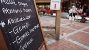 """Ein Hinweisschild auf die 3G-Regel (""""Geimpft, getestet, genesen"""") steht vor einem Lokal. © picture alliance/dpa Foto: Oliver Berg"""