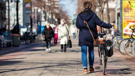 People go through a pedestrian zone.  © Picture Alliance Photo: Moritz Frankenberg