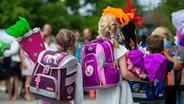 Kinder stehen mit Ranzen auf dem Rücken und Schultüten in den Händen auf dem Schulhof. © dpa-Bildfunk Foto: Philipp Schulze