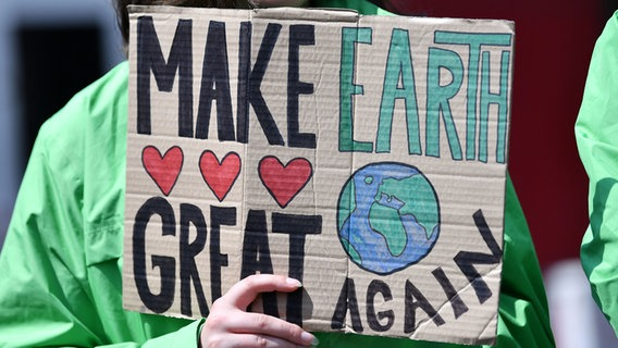 "Person hält Protestplakat: ""Make Earth Great Again"" © dpa-Bildfunk Foto: Martin Schutt"