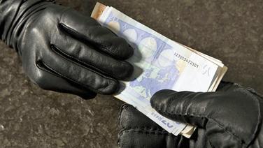 Euroscheine wechseln von einer Hand in schwarzem Lederhandschuh zu einer anderen. © blickwinkel/picture alliance Fotograf: McPHOTOs