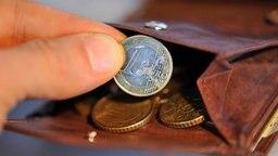 Eine Hand hält eine Münze. © dpa Bildfunk Foto: Andreas Gebert