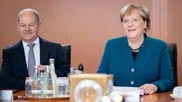 Der Bundesfinanzminister Olaf Scholz (SPD) und Bundeskanzlerin Angela Merkel (CDU) sitzen bei einer Sitzung zur Halbzeitbilanz der Großen Koalition an einem Tisch. © dpa - Bildfunk Foto: Kay Nietfeld