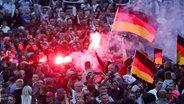 Demonstranten der rechten Szene zünden Pyrotechnik und schwenken Deutschlandfahnen. © dpa-Bildfunk Fotograf: Jan Woitas