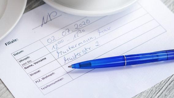 Ein Formular zur Erhebung der Kontaktdaten liegt in einem Café auf einem Tisch. © picture alliance/Hauke-Christian Dittrich/dpa Foto: Hauke-Christian Dittrich