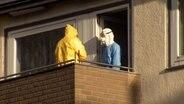 Zwei Männer in Schutzanzügen auf einem Balkon bei Sonnenschein. © HannoverReporter