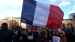 Eine Frau bei einer Kundgebung schwenkt eine französische Flagge. © TeleNewsNetwork