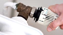 Eine Frau dreht am Thermostat einer Heizung. © dpa-Bildfunk Foto: Hauke-Christian Dittrich/dpa
