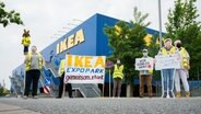 Beschäftigte der Möbelhauskette Ikea stehen mit einem Stoffelch und einem Transparent bei einem Streik vor dem Ikea-Expopark. © dpa-Bildfunk Foto: Julian Stratenschulte