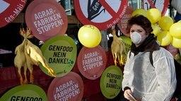 Campact-Aktion: Eine junge Frau mit Mundschutz protestiert gegen gentechnisch veränderte Nahrungsmittel. © Picture Alliance