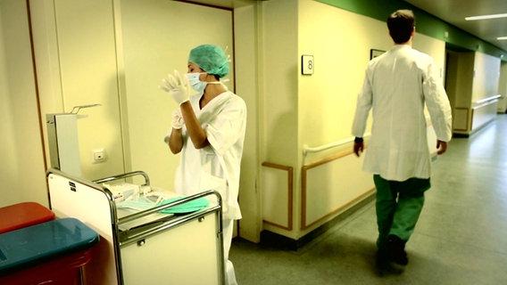 Eine Krankenschwester und ein Arzt gehen auf dem Flur eines Krankenhauses. © NDR
