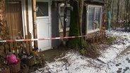 Der Eingang einer Gartenlaube ist mit Polizeiband abgesperrt. © NDR